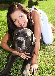 Young beautiful teen plays with her dog in the yard