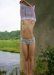 Young russian schoolgirl poses nude near river.